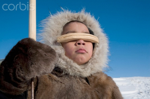 Gjoa Haven is a town in the far north of the Northwest Territories in Canada where over 1000 Inuits live. Here a boy wearing snow goggles holds a hunting spear.